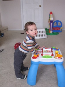 He stood at a toy (with the stabilizing support of his leg braces) at 15 months.